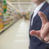 Choice of buying for health concept : Businessman finger touching with supermarket blur background.